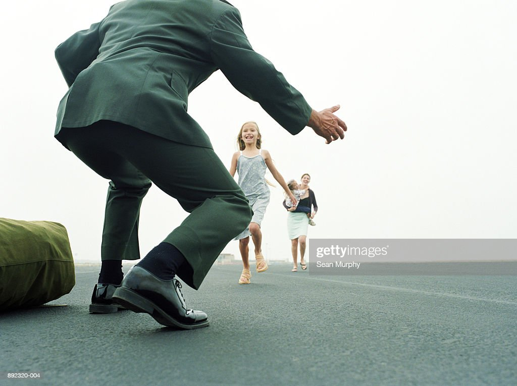 Family running to greet soldier at military base : Stock Photo