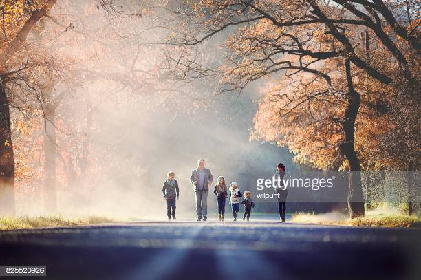 Family running together between autumn trees