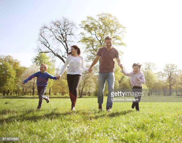a family running together in a park - four people stock pictures, royalty-free photos & images