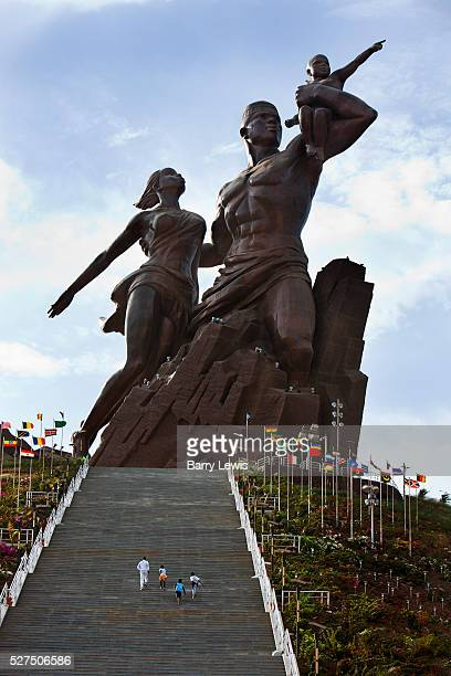 A family running up the steps leading to the African renaissance statue Dakar Senegal An enormous mound of bronze rising from the rubble of Dakar The...