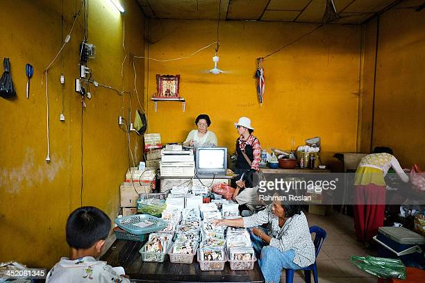A family runs an illegal DVD shop in a wet market on November 26 2013 in Siem Reap Cambodia Cambodian continues their daily life despite a...