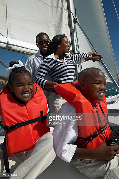 family sailing on a yacht with the children wearing life jackets - 救命胴衣 ストックフォトと画像