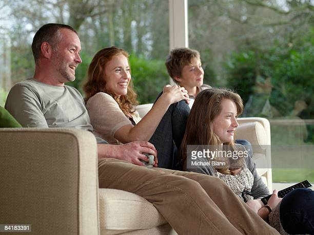 Family sat at home on sofa watching TV