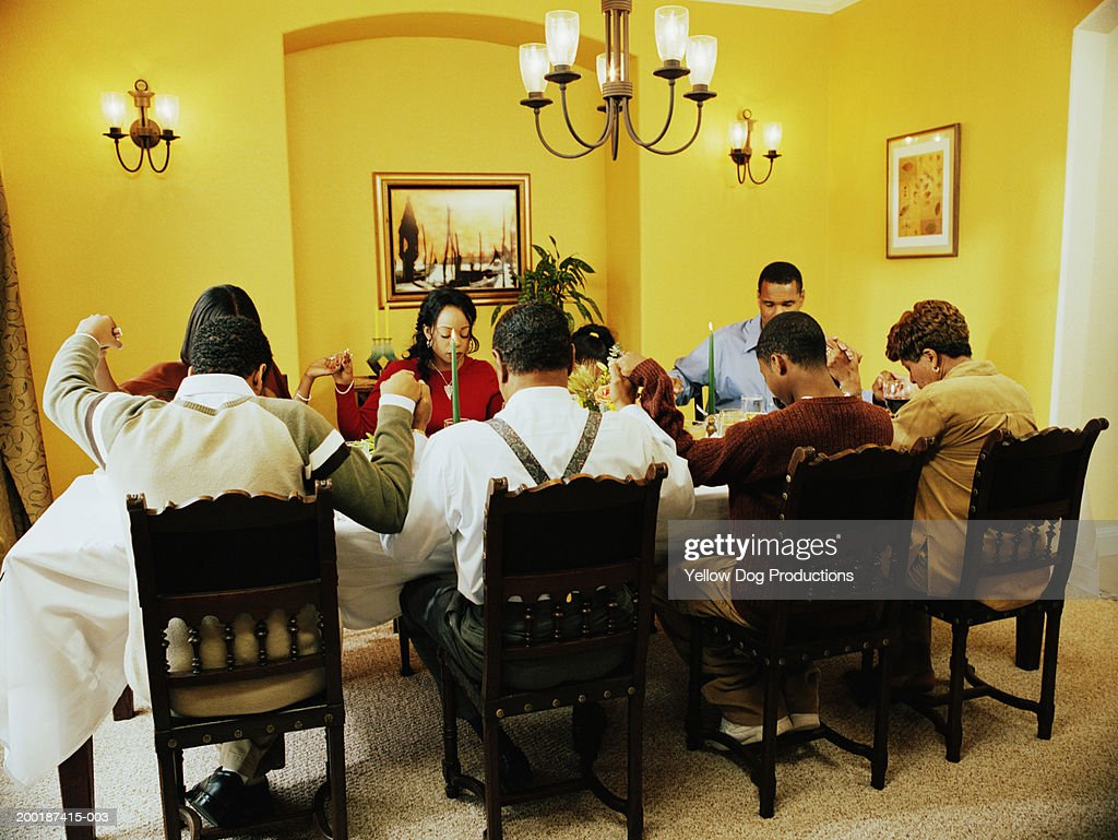Family saying grace at dinner table : Stock Photo