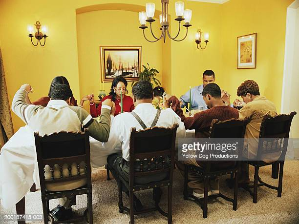 family saying grace at dinner table - thanksgiving dog stock photos and pictures