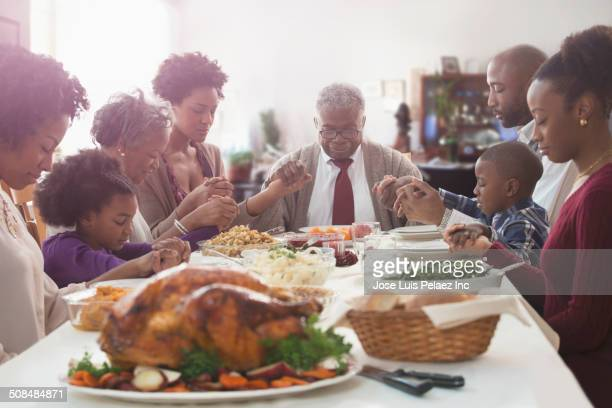 family saying grace at holiday table - black family dinner stock photos and pictures
