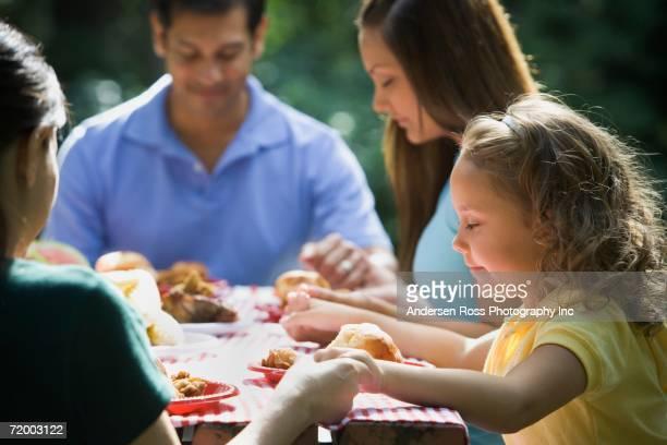 Family saying grace at picnic table
