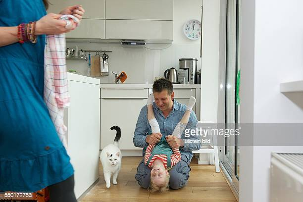 A father is doing with his little daughter in the kitchen on the kitchen floor In the foreground the mother with a kitchen towel A white house cat...
