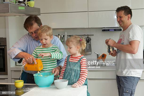 Family Scene: A little boy and a little girl baking a cake together. The grandfather is visiting and holding the hand mixer. The father stands in the...