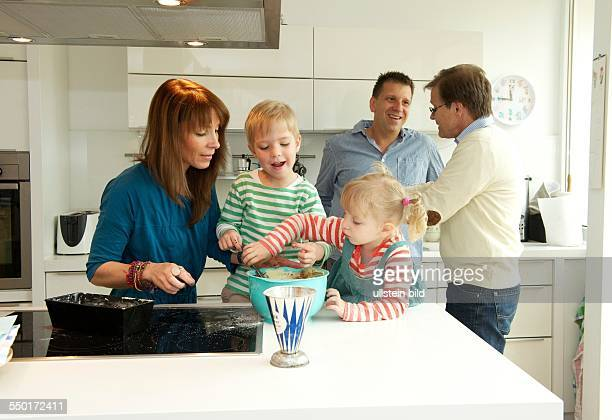 A little boy and a little girl with her mother baking a cake In the meantime father and grandfather discuss in the kitchen Aachen