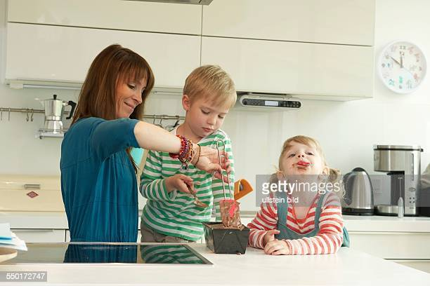A little boy and a little girl with her mother baking a cake in the kitchen Aachen