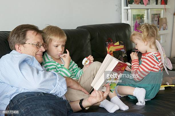 The Grandfather reads a little boy and a little girl from a children's book in front of a story Grandfather and grandchildren are sitting on the sofa...