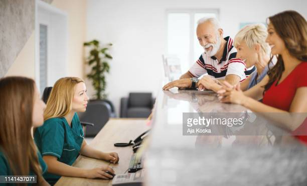 family scheduling a preventive visit at medical clinic. - medical receptionist uniforms stock photos and pictures
