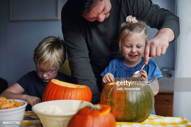 Family scooping out pumpkins together for Halloween