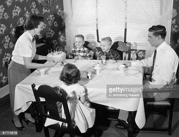 Family seated dinner table, mother standing, holding birthday cake.