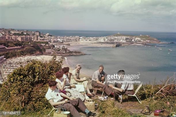 Family seated on chairs to enjoy a picnic at Porthminster Point overlooking Porthminster Beach and the harbour and town of St Ives in Cornwall,...