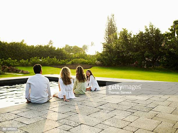 Family seated on edge of tropical resort pool
