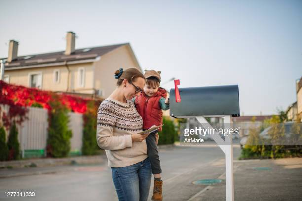 family sending or receiving mail with mailbox near house - family politics stock pictures, royalty-free photos & images