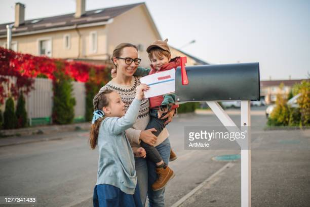 family sending or receiving mail with voting ballot using mailbox near house - voting by mail stock pictures, royalty-free photos & images