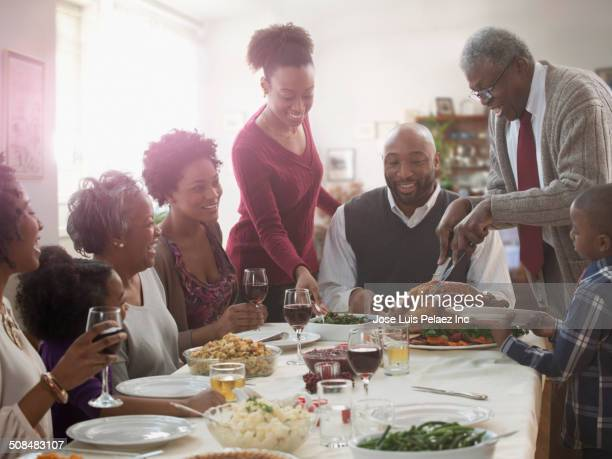 family serving each other at holiday table - black family dinner stock photos and pictures