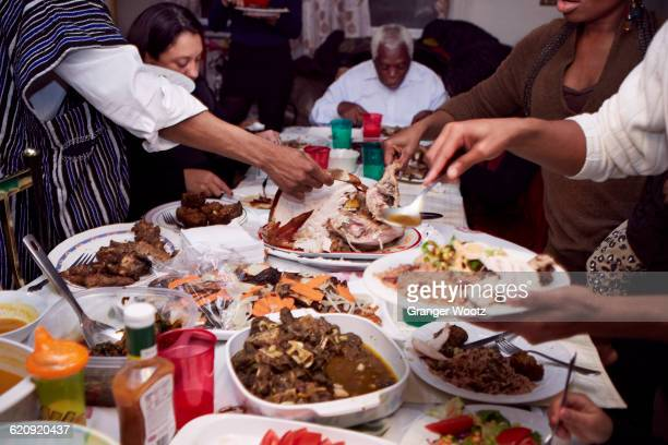 family serving food at holiday dinner - black family dinner stock photos and pictures