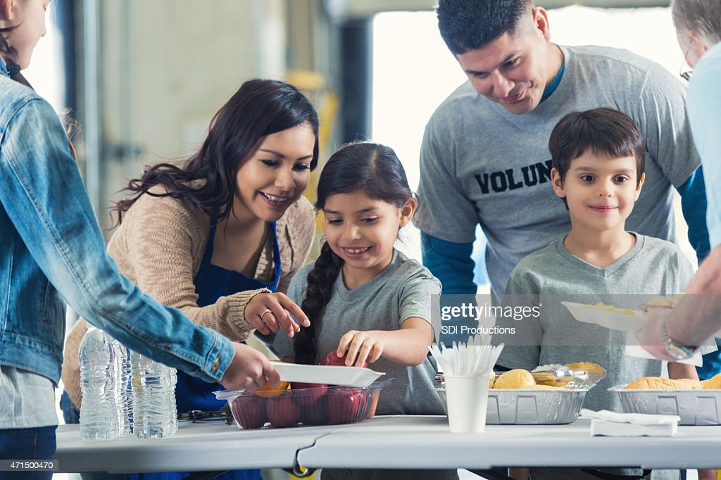 Family serving meals while they volunteer in soup kitchen together : Stock Photo