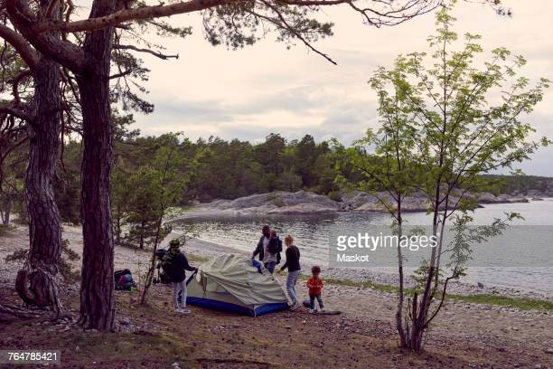Family setting tent by trees at beach