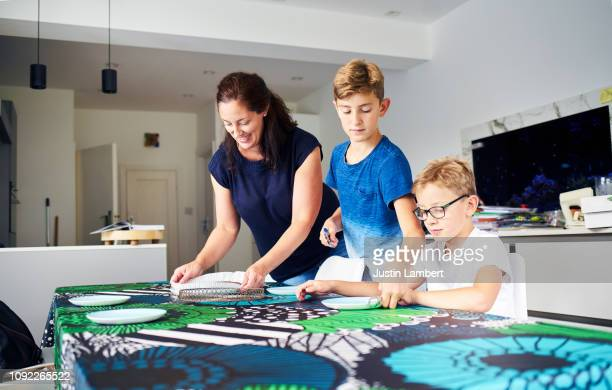 family setting the table ready for a meal together in the kitchen - saltdean stock pictures, royalty-free photos & images