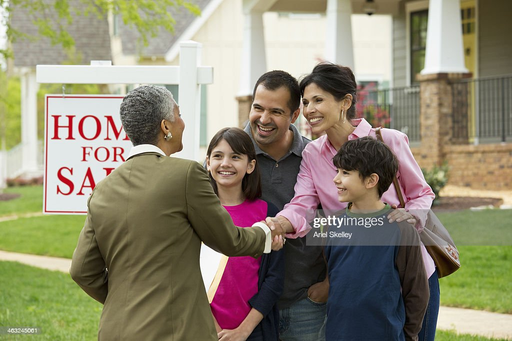 Family shaking hands with realtor at new house : Stock Photo