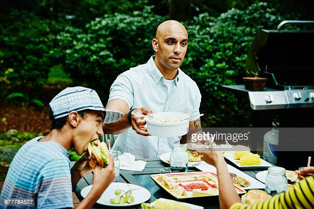 Family sharing dinner at table in backyard