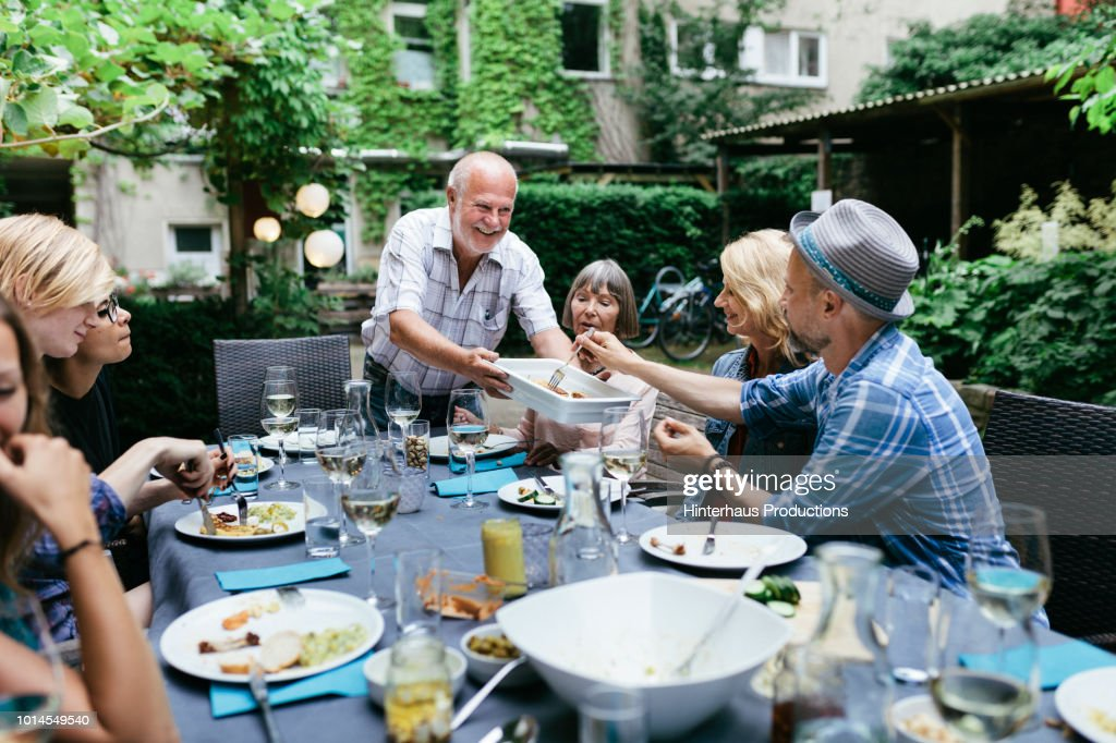 Family Sharing Food At BBQ In Courtyard Together : Foto de stock