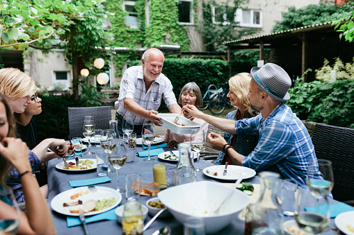 Family Sharing Food At BBQ In Courtyard Together - gettyimageskorea