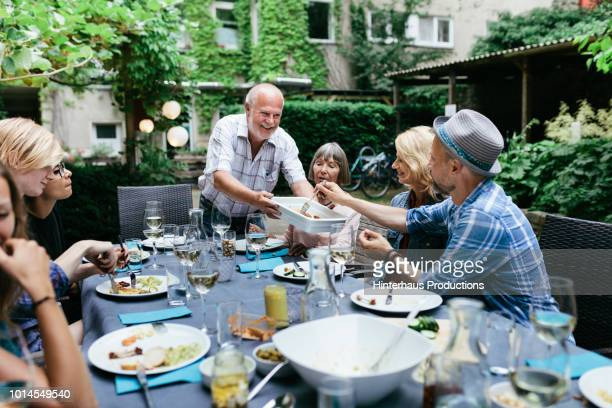 family sharing food at bbq in courtyard together - essen mund benutzen stock-fotos und bilder
