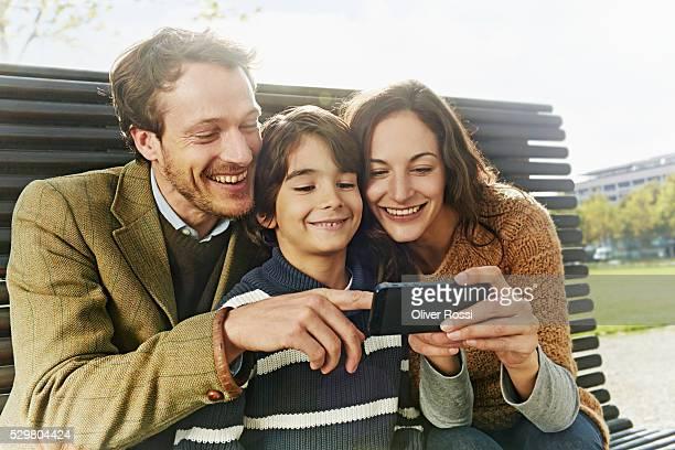 Family sharing tablet in park
