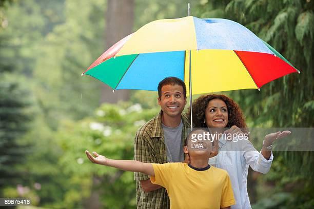 Family Sharing Umbrella During Rain Shower