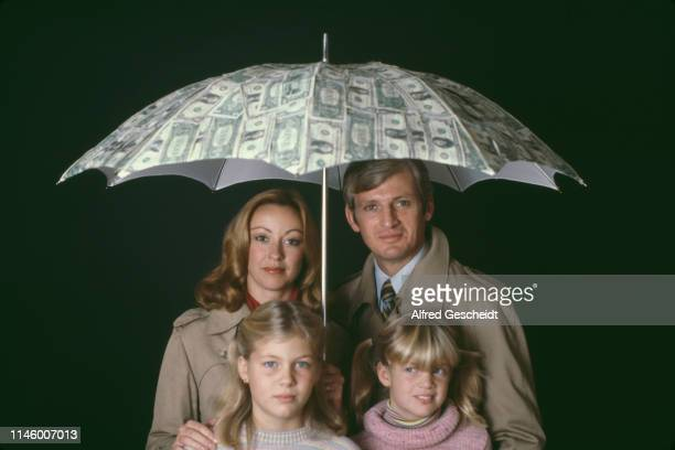 A family shelters under a dollar printed umbrella US 1979