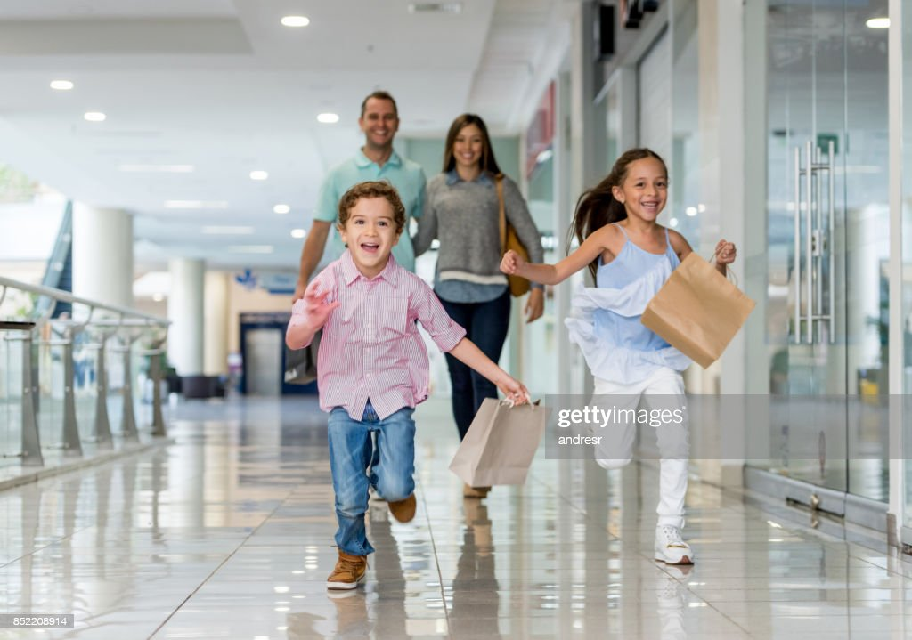 Family shopping and running towards the camera at the mall : Stock Photo
