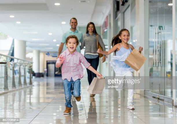 family shopping and running towards the camera at the mall - shopping mall stock pictures, royalty-free photos & images