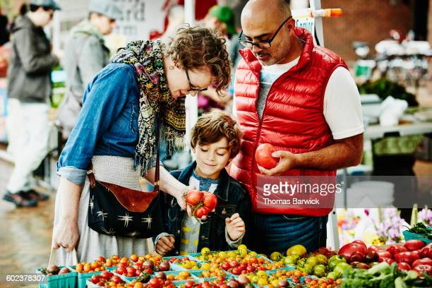 family shopping at organic farmers market - family with one child stock pictures, royalty-free photos & images