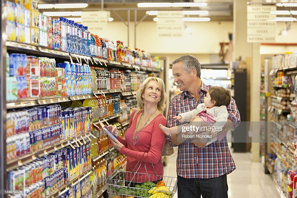 Family shopping for groceries in supermarket : Stock Photo