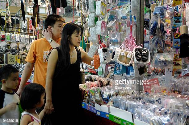 A family shops at a neighborhood night market in Singapore on Monday Sept 14 2009 Singapore's retail sales dropped more than expected in July a...