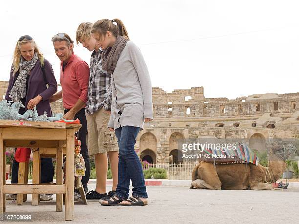 family shops for souvenirs beside roman colliseum - tunisia stock pictures, royalty-free photos & images