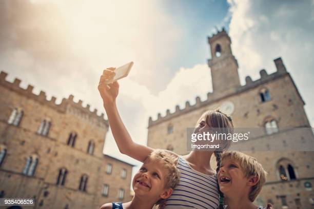 family sightseeing italian town of volterra, tuscany - volterra stock photos and pictures