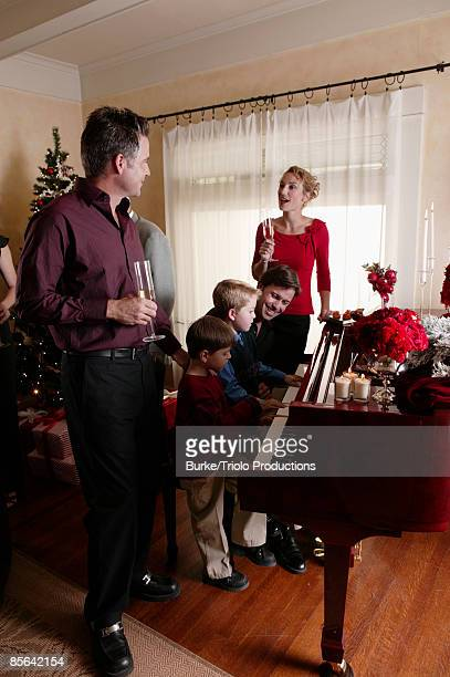 Family singing around piano