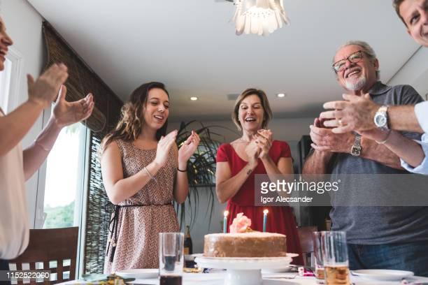 familia cantando felicitaciones con torta en la mesa y velas - aniversario fotografías e imágenes de stock