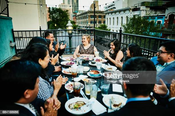 Family singing happy birthday for woman during dinner on restaurant deck