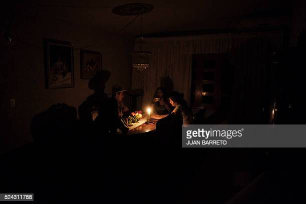 A family sit at a candle lit table in the state of Barinas 600 km west of Caracas on April 25 2016 Recessionhit Venezuela will turn off the...