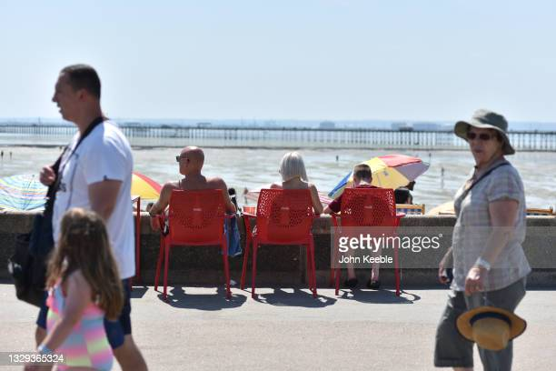 Family sit on plastic chairs on the promenade as crowds gather to enjoy the warm sunny weather on Jubilee beach on July 18, 2021 in Southend-on-Sea,...