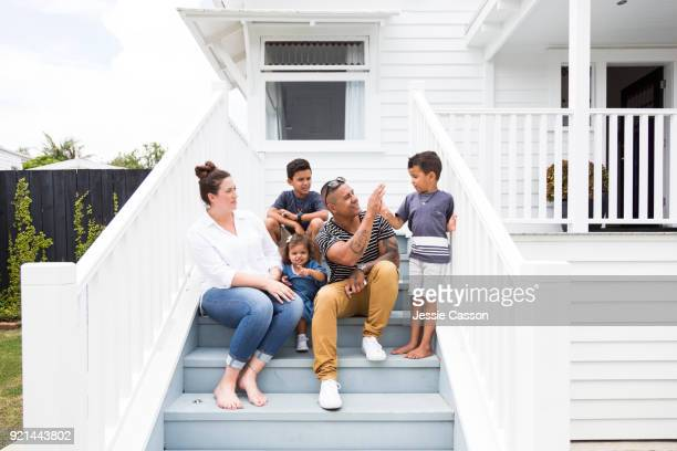 Family sit on steps outside their home