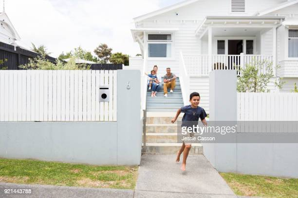 Family sit on steps outside their home while their children run down steps
